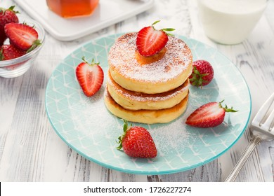 Cottage cheese pancakes with sliced strawberry on white background for breakfast.