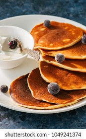 Cottage cheese pancakes with sour cream and berries on a white plate on a blue stone background.