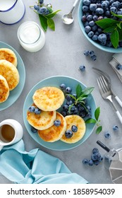 Cottage cheese pancakes, sweet curd fritters with berries, syrniki with honey and fresh blueberry on breakfast table