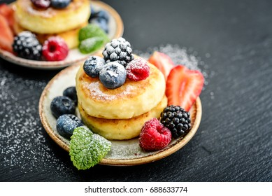 Cottage cheese pancakes, syrniki, curd fritters with fresh berries on black slate background