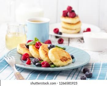 Cottage cheese pancakes. Syrniki, milk, berry