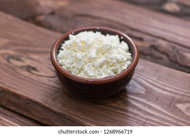 Cottage cheese in a plate on a wooden background.