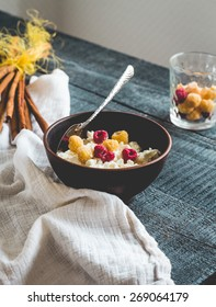 cottage cheese with raspberries in a dark clay plate, cinnamon sticks, breakfast, on a blue wooden background
