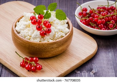 cottage cheese with red berries and mint in a wooden bowl/cottage cheese with red berries and mint in a wooden bowl. selective focus