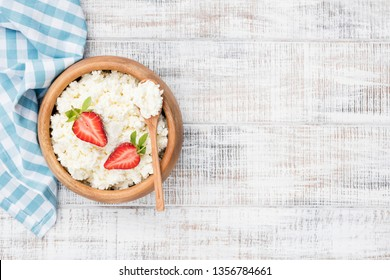 Cottage cheese, tvorog or curd in wooden bowl, white wooden planks background. Top view and copy space