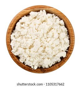 Cottage cheese in a wooden bowl isolated on a white background. Top view. Flat lay