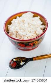 Cottage cheese in wooden khokhloma tableware, vertical shot