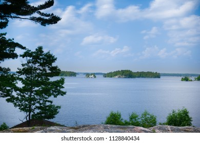 Cottage country landscape in Ontario. A white cottage facing the calm waters is visible on the lake horizon.