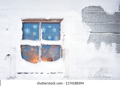 Cottage covered with frost and snow in winter. Candlelight glowing through window.