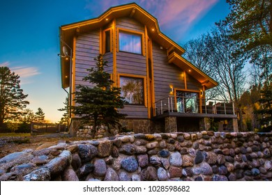 Cottage decorated with natural stone. Cottage with balcony. Two-storey house. Wooden house. Living in nature. Finishing natural stone.