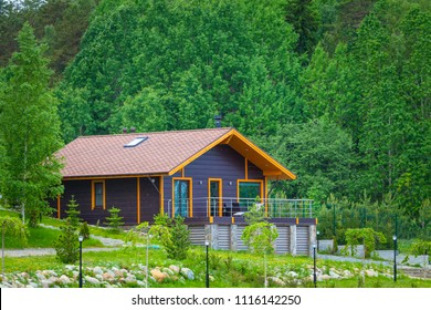 Cottage. A house in the background of trees. Vacation home. The cottage is brown. Well-groomed area near the Cottage. Living in the country.