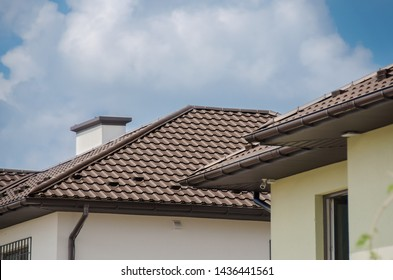 Cottage house with the brown roof of metal tile.