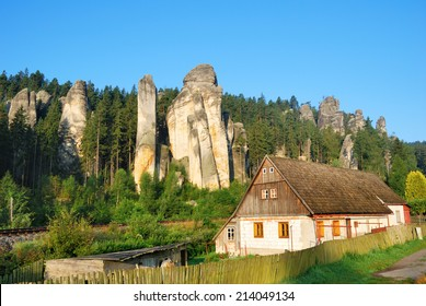 Cottage house with forest and sandstone towers behind