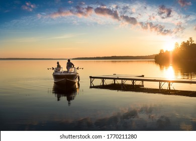 Cottage Life - Father and son fishing on a boat at sunrise/sunset at the peaceful cottage in Kawartha Lakes Ontario Canada on Balsam Lake