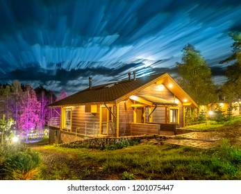 Cottage on the background of the night sky. House with street lighting. Living outside the city. Two-storey house. Wooden cottage.