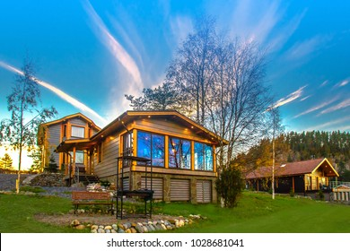 Cottage on the slope. Cottage village. House with large windows. The construction of the mysterious houses. Infrastructure. Living in the country. Wooden house.