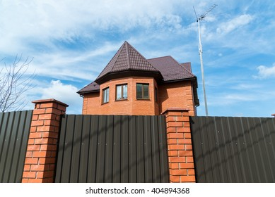 Cottage from a red brick behind a high fence