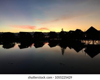 Cottage resorts on the lake background sunset