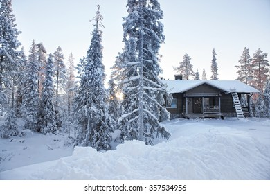 Cottage in a snow covered forest in sunrise in Ruka village in Finland on the Arctic pole circle in winter - Shutterstock ID 357534956