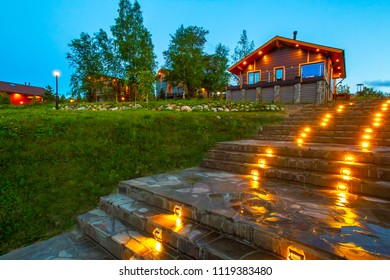 Cottage. Stone staircase in the cottage village. Track lighting. Street lighting at home. Concrete stairs with light. The path is lined with natural stone. House on a hill.