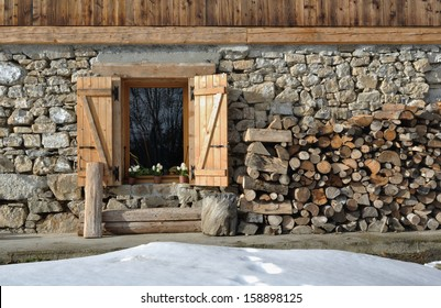cottage of stone and wood with pile of firewood