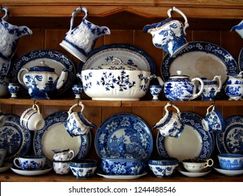 Cottage style kitchen decoration with shelves displaying blue and white British porcelain tea sets.