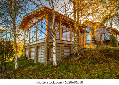 The cottage is surrounded by trees. Cottage with panoramic windows. Glazing of houses. House with large windows. The glazed facade of the house.