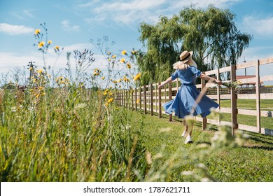 Cottagecore Farmcore Countrycore aesthetics, fresh air, countryside, slow life, pastoral life, outdoor picnics, wearing grandma clothes. Young girl in straw hat with flowers walks on country farm.