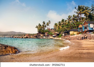 Cottages near lagoon in sunny day at Dreamy tropical Palolem beach in Goa, India