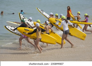 """COTTESLOE BEACH, WESTERN AUSTRALIA, 7 DEC 2014: A group of youths start to compete in a board race at Cottesloe Beach.  Young surf lifesavers are also known as """"Nippers""""."""