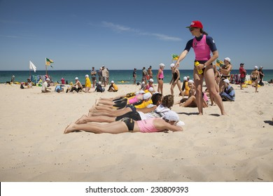 """COTTESLOE, WESTERN AUSTRALIA, 16 NOVEMBER 2014: Young children taking part in a """"flag race"""" as they train to be surf lifesavers at Cottesloe Beach.  Young surf lifesavers are known as """"Nippers""""."""