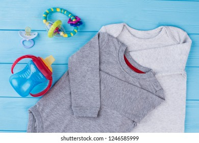 Cotton baby creepers and toys. Blue wood background.