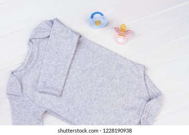 Cotton baby onesie and pacifiers. White wood background.