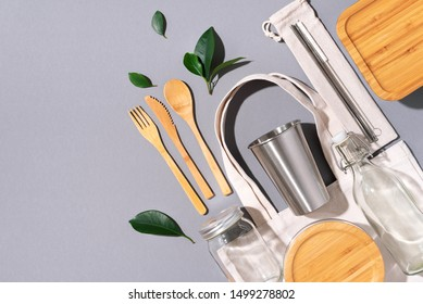 Cotton bags, glass jar, bottle, metal cup, straws for drinking, bamboo cutlery and boxes on gray background. Sustainable lifestyle. Zero waste, plastic free shopping concept