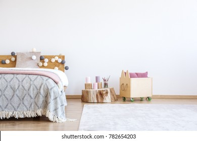 Cotton balls lights hanging on wooden bedhead in white room with stump, animal shaped box and bed