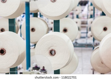 cotton cones stacked in a big rack in a yarn factory