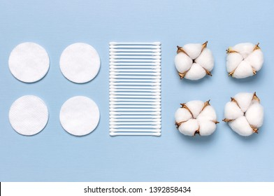 Cotton Cosmetic Makeup Removers Tampons. Spa concept. Flat lay background with cotton flowers, cotton pads, eared sticks. Hygienic sanitary swabs on blue background Top view copy space
