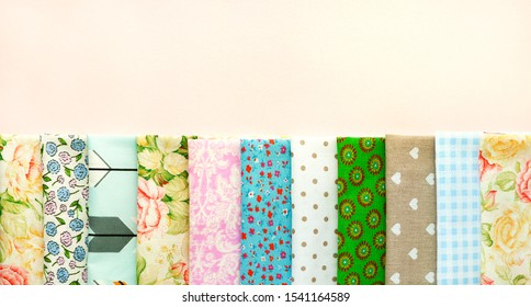 Cotton fabric in different colors and patterns. Panorama in the form of cotton fabric on a pink background. Natural fabric for sewing clothes and bedding.