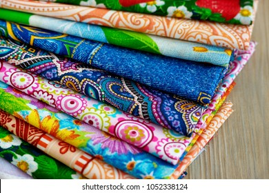 Cotton fabric is folded in a fan-shaped manner. Cotton fabric for sewing clothes and bedding. Chintz, satin, coarse calico composed of layers. Multicolored cotton fabric.