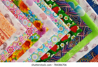 Cotton fabric is folded into an angle. Many different fabrics made of cotton. Satin, calico and cotton for sewing clothes and bed linen. Multicolored cotton fabric. View from above.