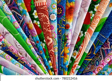 Cotton fabric folded into strips. View from above. Many multi-colored cotton fabric. Satin, coarse calico, poplin, chintz for sewing clothes and bed linen. Cotton fabric with beautiful patterns.