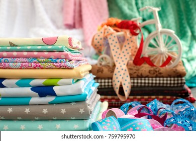 A lot of cotton fabric for sewing. Cotton fabric for sewing clothes and bed linen. Fabric satin is piled in a pile. Many satin colored ribbons and textiles. Cloth and decorative bicycle.