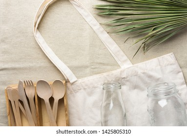 Cotton fabric tote bag wooden flatware cutlery crystal jar bottle green palm leaf on linen background. Plastic-free alternatives zero waste environmental protection nature friendly living