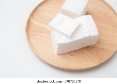 Cotton for facial cleansing wipes on wooden plate.