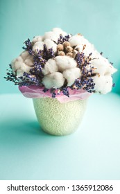 Cotton and lavandin mixed dry flowers bouquet in a white vase, blue background