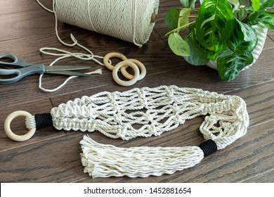 A cotton macrame plant hanger is displayed next to some crafting supplies on a hardwood floor.