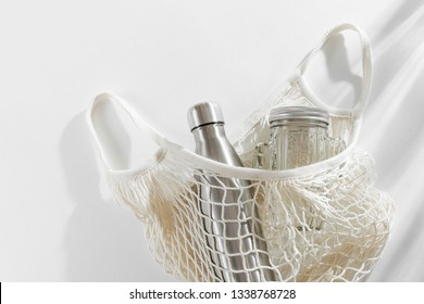 Cotton net bag with reusable metal water bottle, glass jar and straw. Zero waste concept. Eco friendly