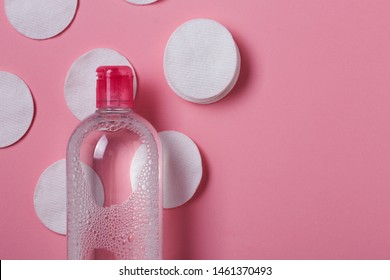 Cotton pads and bottle with micellar cleansing water on pink background. Beauty skin care, make up removal and face cleansing