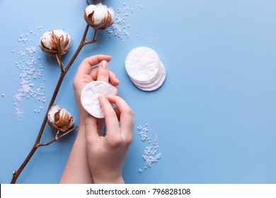 Cotton pads for removal makeup with woman hands cotton flowers on the blue background flatlay