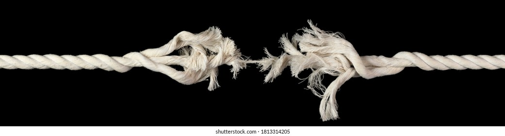 Cotton rope, frayed and ready to break apart with rope held together by last strand ready to snap. Concept of danger or stressful situation like divorce separation, deadlines, failure, or tension.